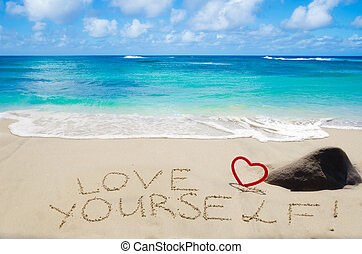 """Sign """"Love yourself"""" with heart on the sandy beach by the ocean"""
