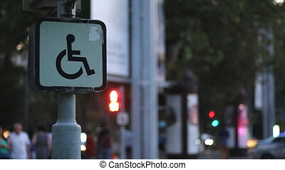 Sign of a disabled person sitting on a wheelchair against the background of blurred walking people. Concept idea
