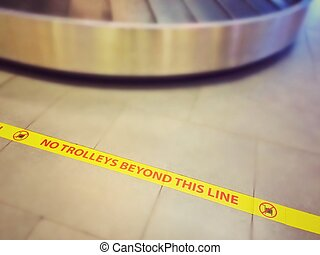 """Sign of """"No trolley beyond this line"""" in the airport, luggage drop area, vintage effect"""