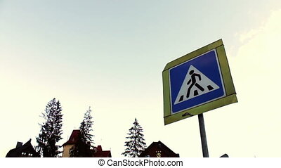 Sign of the pedestrian crossing on background sky and houses.
