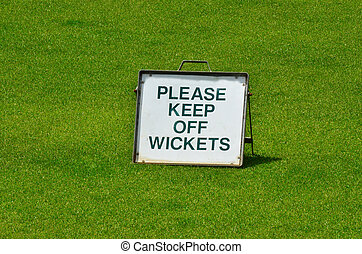 "Please keep out off wickets - Sign on green grass reads: ""..."