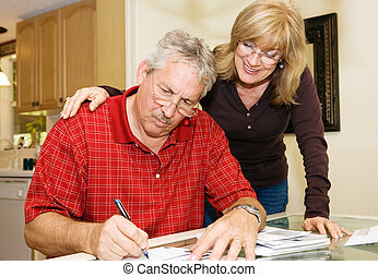 Mature couple at home signing paperwork together.