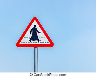 Sign prohibiting traffic for pedestrians in a southern Arab country, a silhouette of a pedestrian in traditional clothes, against a blue sky