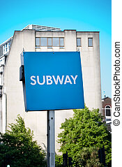 Sign showing subway in an urban setting
