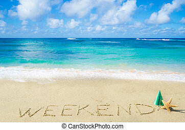 """Sign """"Weekend"""" on the sandy beach"""