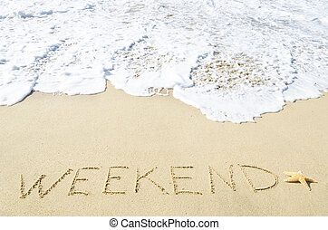 "Sign ""Weekend"" on the sandy beach"
