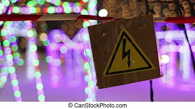 sign with a picture of caution high voltage on the...