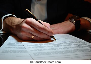 Signature of the document - The businessman signs documents...