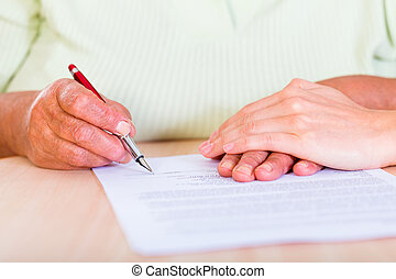 Signature - Photo of an elderly woman sign the testament