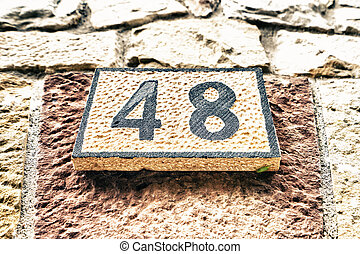 Signboard with number 48 on stone wall