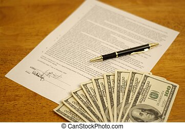 Signed contract with pen, and money on top. Bills...