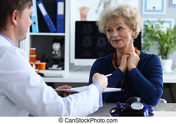 Signing by patient medical intervention document. Doctor gives elderly woman medical document for signature. Doctor hands patient document for examination, table lies device for measuring pressure.