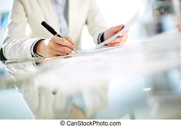 Signing paper - Hands of young businesswoman signing paper