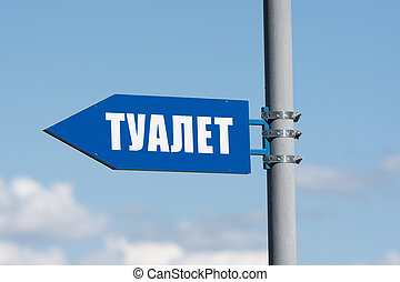 """Signpost on the street in the form of an arrow and the words """"toilet"""""""