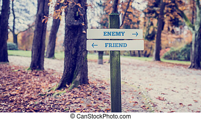 Signpost with arrows pointing two opposite directions towards Enemy and Friend