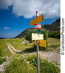 signpost with different directions standing on start of tourist