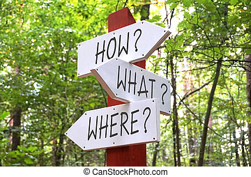 Signpost with three arrows - how, what, where questions
