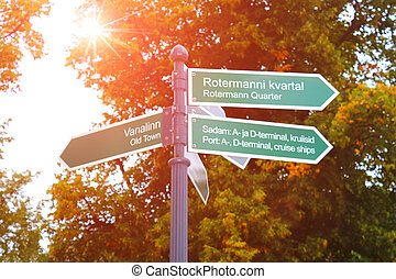 Signposts to the Old Town, Rotermann quarter and port in Tallinn, Estonia. Against the background of autumn foliage. Morning, sun light.