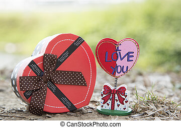 Signs of love with heart-shaped gift natural background
