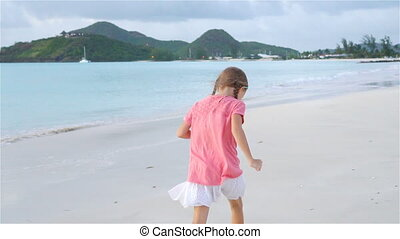 Sihouette of little girl walking on the beach at sunset.