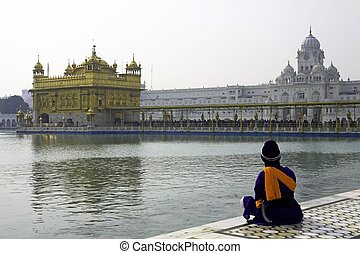 Sikh Man sitting on Marble steps of Tank surrounding the  Golden Temple