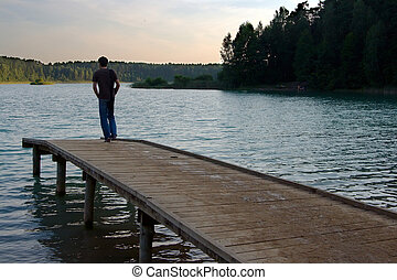 Silence Lakeside - man standing on a jetty lakeside watching...