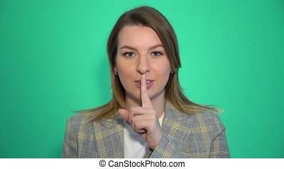 Silence, please Close up portrait of young woman holding her forefinger on lips showing hush silence sign, standing over green background