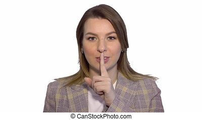 Silence, please Close up portrait of young woman holding her forefinger on lips showing hush silence sign, standing over white background