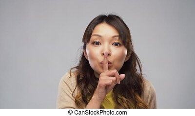 asian woman making shush gesture - silence, privacy and...