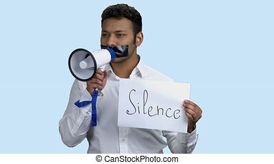 Silenced Indian man holding megaphone. Young man with taped mouth holding card with inscription Silence. Censorship concept.