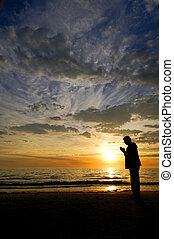 Silent Prayers - A man praying on the beach in front of a...