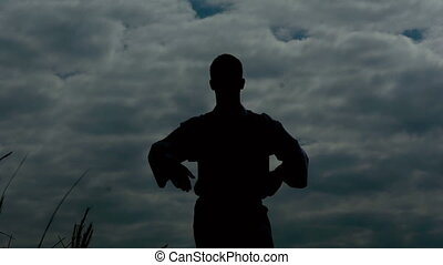 Silhouete of man stands on the rock with raised arms on sky background. Slowly