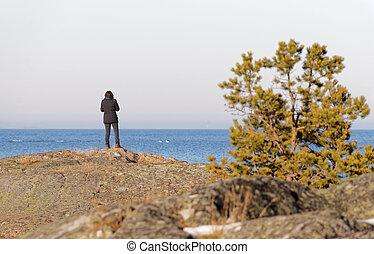 Silhouett of a thoughtful woman looking at the sea