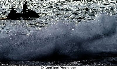 silhouette, a men on a motorbike floats on the sea. -...