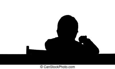 Silhouette A son drawing at the table at home