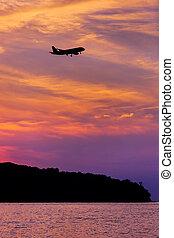 Silhouette above Passenger Airplane Landing at sunset