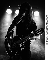 Silhouette acoustic guitar player on stage - Photo of a...
