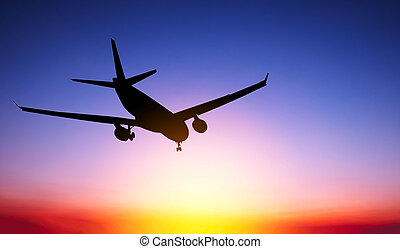 Silhouette airplane at sunset background
