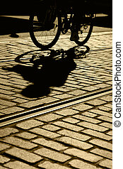 Silhouette and shadow of lone bicycle, brick pavement and street car tracks, focus on shadow, Fisherman's Wharf, San Francisco, California,
