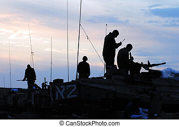 Silhouette of army soldiers preparing their tanks and weapons at sunset