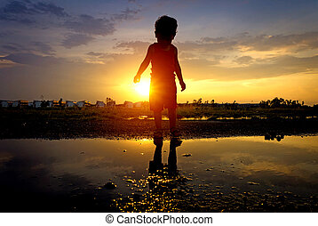 silhouette asian kid and reflection sunset, one boy ...