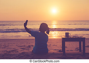 Silhouette asian woman using smartphone on the beach in sunset time,