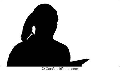 Silhouette Attractive young woman using a touchscreen tablet, reading and talking to a camera.