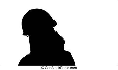 Silhouette Beautiful female engineer in hardhat calling via...