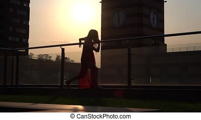 Silhouette Beautiful young girl dancing on the street of a modern city in the sunset light. She is wearing a red dress. Slow motion.