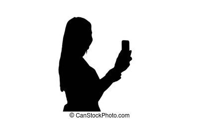 Silhouette Beautiful young woman doing selfies.