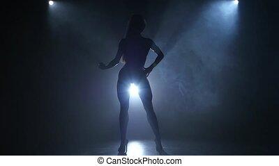 Silhouette bodybuilding girl posing in studio. - Silhouette...