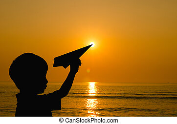 Silhouette boy playing with paper airplane on beach