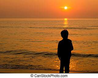 Silhouette Boy standing on the beach with sunrise