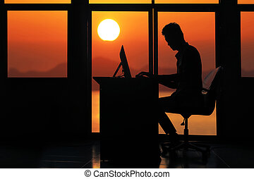 Silhouette business man working on a computer with sunset